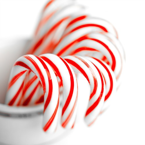 White and red peppermint candy canes in bucket on white background.