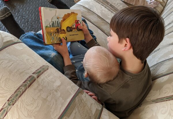 big brother reading to baby
